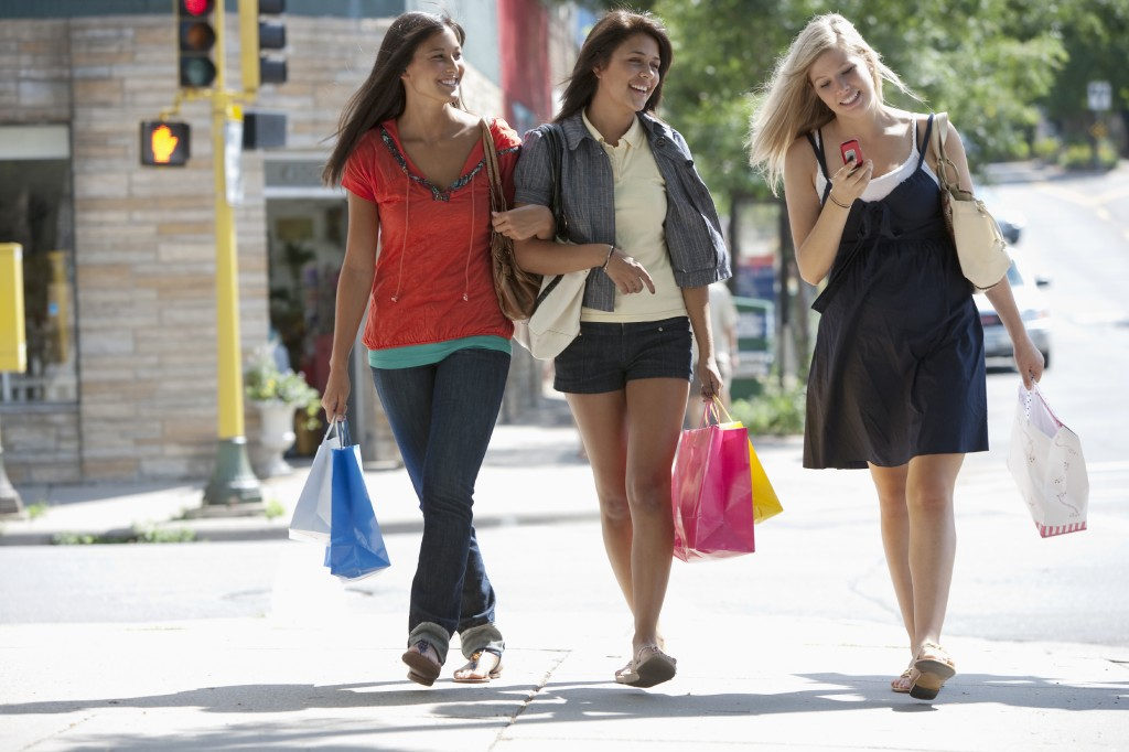 Amis de jeunes femmes shopping et envoyer des SMS sur un téléphone cellulaire