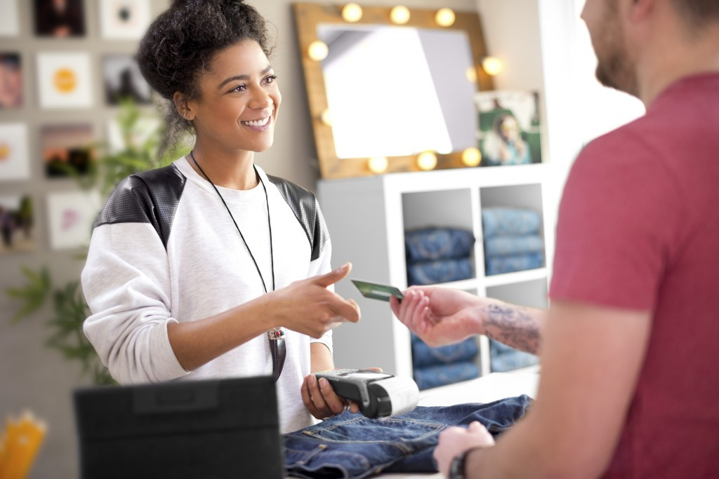 happy sales assistant in clothes store receives payment